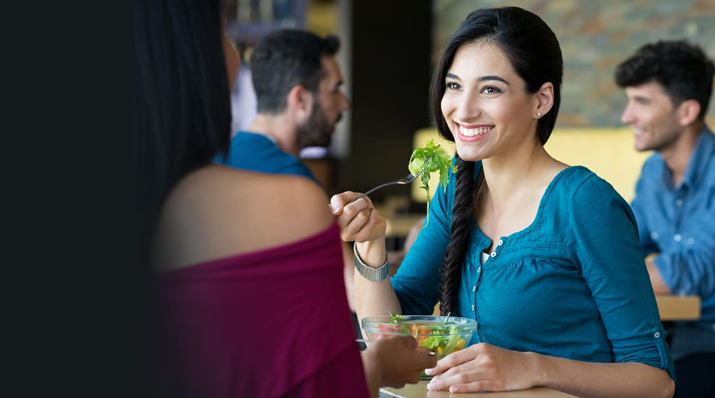 Dartcor Customized Corporate Food Services -smiling woman eating a salad